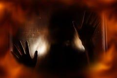 Frauenschatten mit Feuerflammenschirm Stockfotos