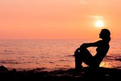Frauenschattenbild, das auf dem Seehintergrund hintergrundbeleuchtet sitzt Stockfotos