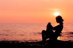 Frauenschattenbild, das auf Seehintergrund sitzt Lizenzfreies Stockbild