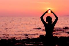 Frauenschattenbild, das in Lotussitz auf dem Seehintergrund hintergrundbeleuchtet sitzt Lizenzfreie Stockbilder