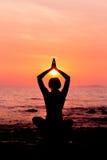 Frauenschattenbild, das in Lotussitz auf dem Seehintergrund hintergrundbeleuchtet sitzt Stockbild