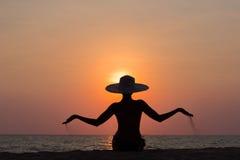 Frauenschattenbild mit dem Hut, der auf Seehintergrund sitzt Lizenzfreie Stockfotografie