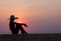 Frauenschattenbild mit dem Hut, der auf Seehintergrund sitzt Stockbild