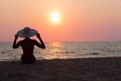 Frauenschattenbild mit dem Hut, der auf Seehintergrund sitzt Stockfotos