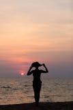 Frauenschattenbild mit dem Hut, der auf Seehintergrund steht Stockfoto