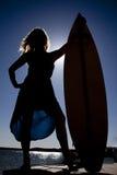 Frauenschattenbild stehen Surfbrett bereit Lizenzfreie Stockbilder