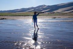 Frauenschattenbild und -reflexion in schimmerndem Wasser Stockbild