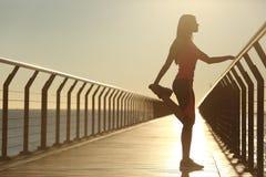 Frauenschattenbild, welches das Ausdehnen auf eine Brücke ausübt Stockfoto