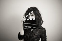 Frauenschauspielerin mustert Porträt hinter Filmscharnierventilbrett stockfotos