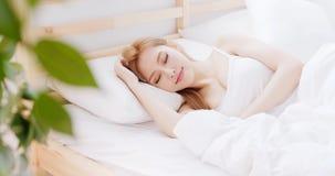 Frauenschlaf auf dem Bett lizenzfreies stockfoto
