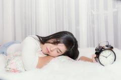 Frauenschlaf auf dem Wohnzimmer und wacht früh bei o'cloc zehn auf Stockfoto