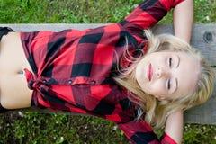 Frauenschlafen entspannt auf einer Bank Stockbild