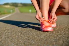 Frauenschnürenlaufschuhe bevor dem Trainieren Lizenzfreies Stockbild