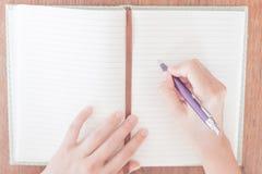 Frauenschreiben auf ihrem Notizbuch Lizenzfreies Stockfoto