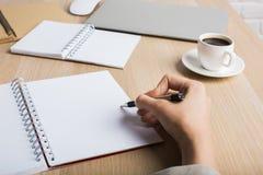 Frauenschreiben in der Notizblockseite Lizenzfreie Stockfotos