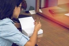 Frauenschreiben in einem Buch mit einem Bleistift Lizenzfreies Stockfoto