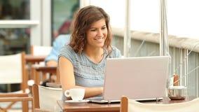 Frauenschreiben in einem Laptop in einer Kaffeestube stock video
