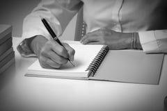 Frauenschreiben im gewundenen Notizblock gesetzt auf den hellen Desktop mit Th Lizenzfreies Stockfoto