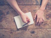 Frauenschreiben im Notizblock am Holztisch Stockfoto