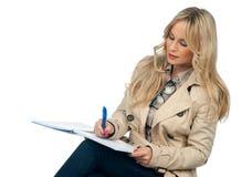 Frauenschreiben im Notizbuch Stockfotografie