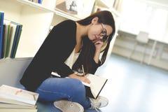 Frauenschreiben im Notizbuch in der Bibliothek Lizenzfreie Stockbilder