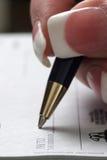 Frauenschreibenscheck lizenzfreies stockbild