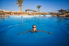 Frauenschwimmen in einem blauen Swimmingpool Stockfotografie