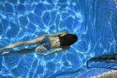 Frauenschwimmen im Pool lizenzfreie stockfotos