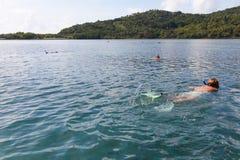 Frauenschwimmen unter bunten Fischen in Thailand Lizenzfreies Stockfoto