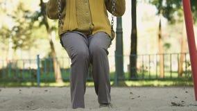 Frauenschwingen von mittlerem Alter, an Kindheits-, sorgloses und glücklichesleben erinnernd stock video