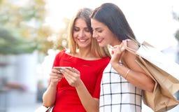 Frauenshows an einem Handy ist etwas zu seiner Freundin Lizenzfreies Stockfoto