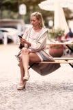 Frauensitzen äußer und Simsen an ihrem Telefon Lizenzfreie Stockfotografie