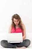 Frauensitzen bequem mit Laptop lizenzfreie stockfotos