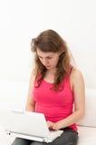 Frauensitzen bequem mit Laptop stockfotos