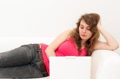 Frauensitzen bequem mit Laptop lizenzfreie stockbilder