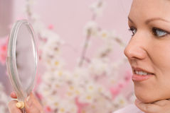 Frauensitzen und -blicke im Spiegel Lizenzfreie Stockbilder