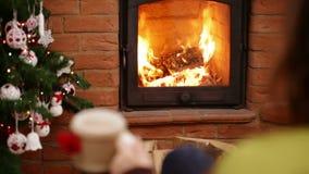 Frauensitzen und Entspannung durch Kamin in einem Schaukelstuhl, der eine Schale zur Weihnachtszeit hält stock video