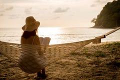 Frauensitzen und -lesung in der Hängematte Lizenzfreie Stockfotos