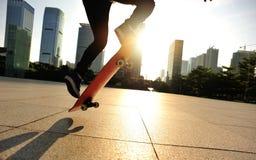 Frauenskateboardfahrer, der an der Sonnenaufgangstadt Skateboard fährt Stockfotos