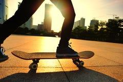 Frauenskateboardfahrer, der an der Sonnenaufgangstadt Skateboard fährt Lizenzfreie Stockbilder