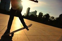 Frauenskateboardfahrer, der an der Sonnenaufgangstadt Skateboard fährt Stockbilder
