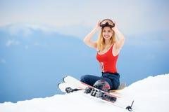 Frauenskifahrer auf die Oberseite des schneebedeckten Hügels mit Skis am Skiort Lizenzfreies Stockbild