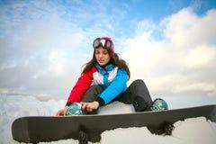 Frauensnowboarder, der sich oben an der Spitze des Berges auf blauem Himmel schnürt Stockbild