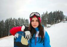 Frauensnowboarder im Winter am Skiort auf Hintergrund der Kiefer Stockbild