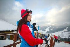 Frauensnowboarder im Winter am Skiort auf Hintergrund des Himmels Stockbild