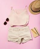 Frauensommerausstattung auf rosa Hintergrund Stockfotografie