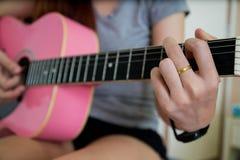 Frauenspielgitarre Lizenzfreie Stockfotos