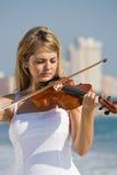 Frauenspielvioline auf Strand Lizenzfreie Stockfotografie