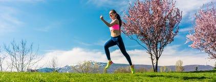Frauensport, der auf Hügel für Eignung läuft Stockfoto