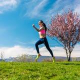 Frauensport, der auf Hügel für Eignung läuft Stockbilder